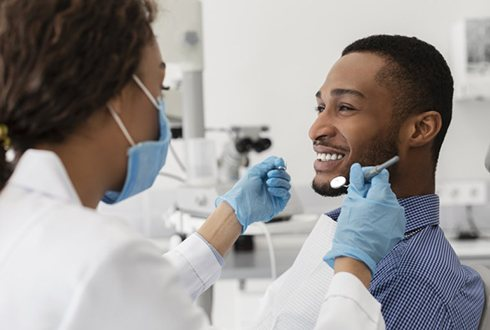 man smiling at his dentist before receiving dental bonding in The Woodlands