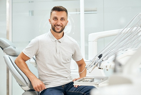 Smiling male patient sitting upright in dental chair