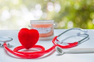 Heart, stethoscope, and model teeth at dental checkup